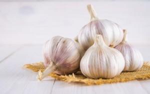 chiodi-di-garofano-di-aglio-e-lampadina-dell-aglio-su-una-tavola-di-legno-bianca_71756-1422